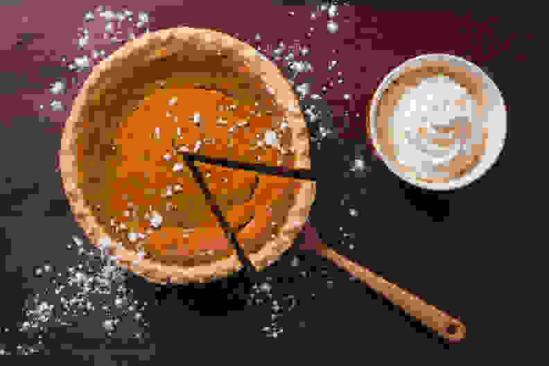 An overhead view of a gourmet pumpkin pie with a side of whipped cream on a rustic wood table surface