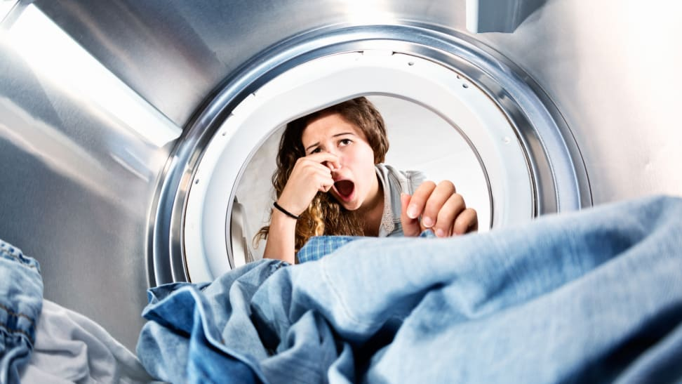 A woman leans into her washing machine and holds her nose