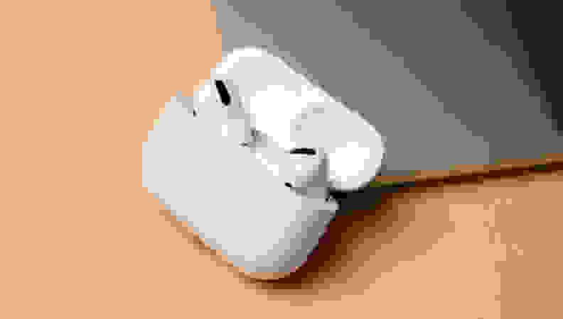 white wireless earbuds in open case on wooden desk