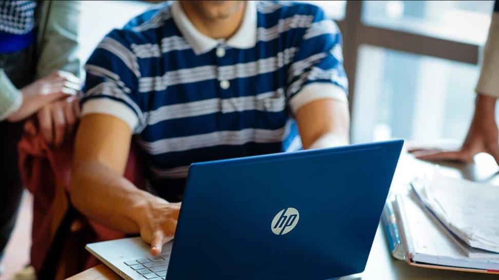 Man typing on HP laptop