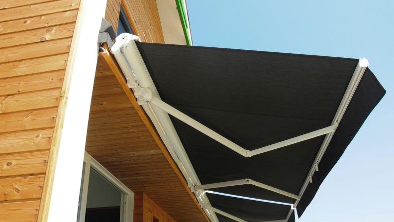 A retractable awning is attached to the side of a house