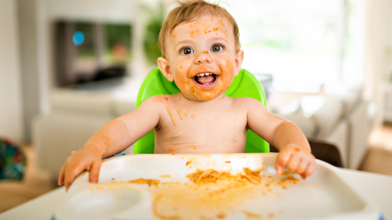 Baby with a face covered in pasta sauce sitting in a high chair.
