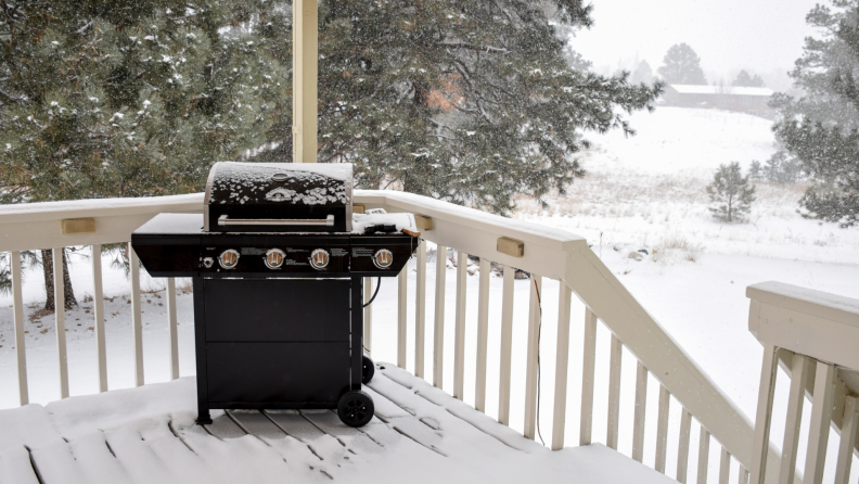 Outdoor grill on snowy deck during winter