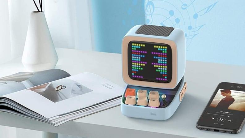 Small, square portable speaker on white desk