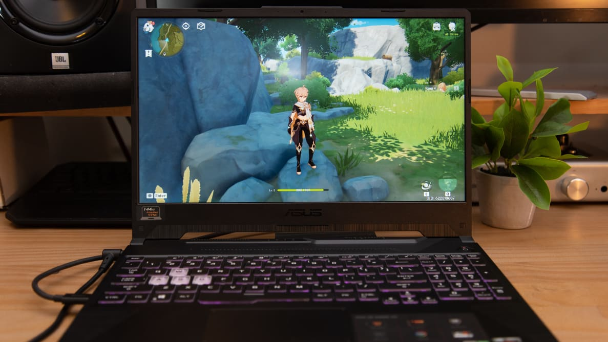 The laptop is on a desk, with a game running on the screen.