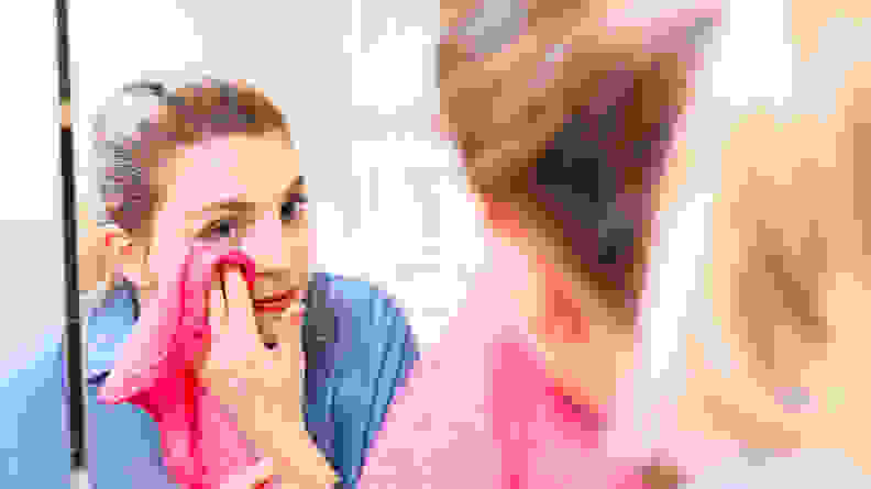 A woman stares into a large mirror and wipes her skin with a hot pink Makeup Eraser towel.