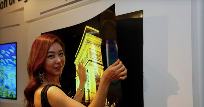 "An LG representative poses with LG's newest prototype—a ""wallpaper"" 55-inch OLED display."
