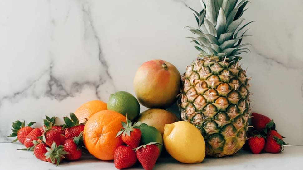 A pineapple, strawberries, mangoes, oranges, and lemons arranged in a pile on a white marble surface.