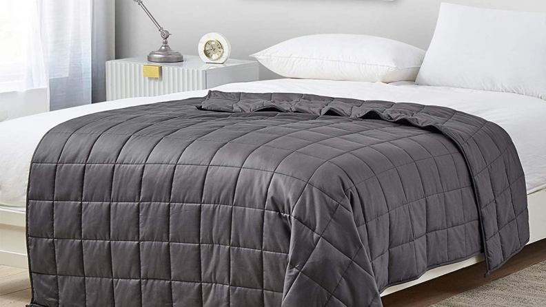 A gray weighted blanket sits on a bed.