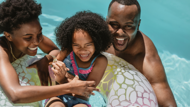 Family of three enjoying fun pool time together with inflatable tube.