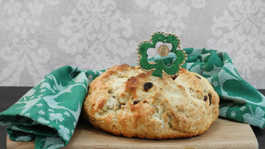 An Irish soda bread is sitting on a cutting board covered with Irish St-Patricks-Day-themed decorations
