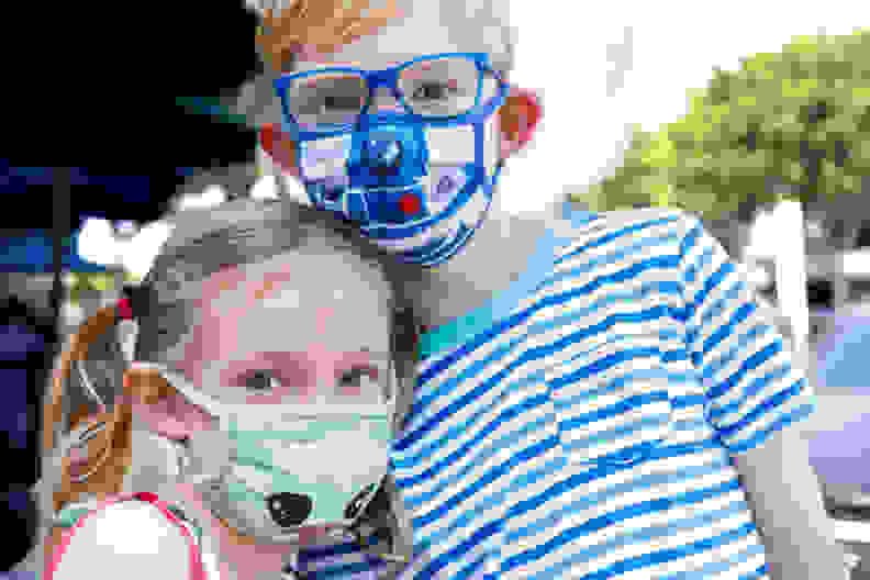 A young girl, wearing a Baby Yoda face mask, hugging a young boy wearing an R2D2 face mask