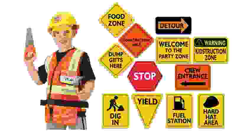 A child in a construction worker costume and a set of construction signs.