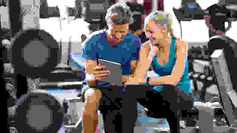 Two people sitting on a workout bench at the gym.