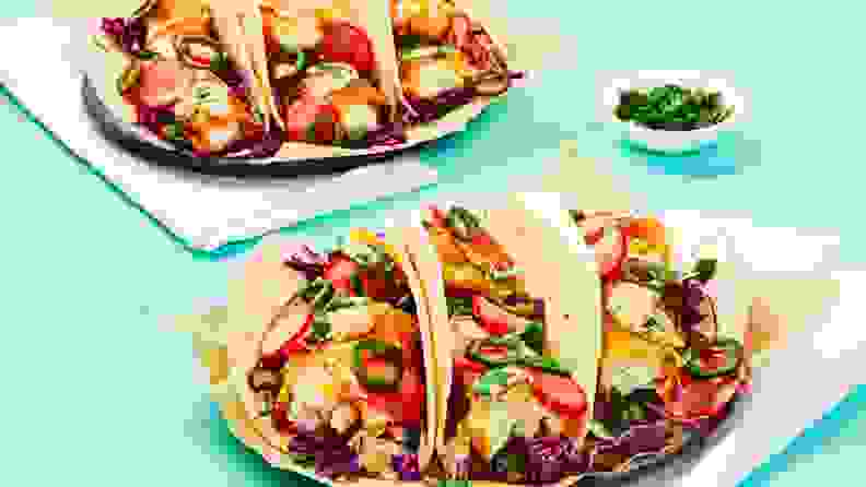 Three fish tacos arranged on a square white plate, accompanied by a second plate of tacos in the background.
