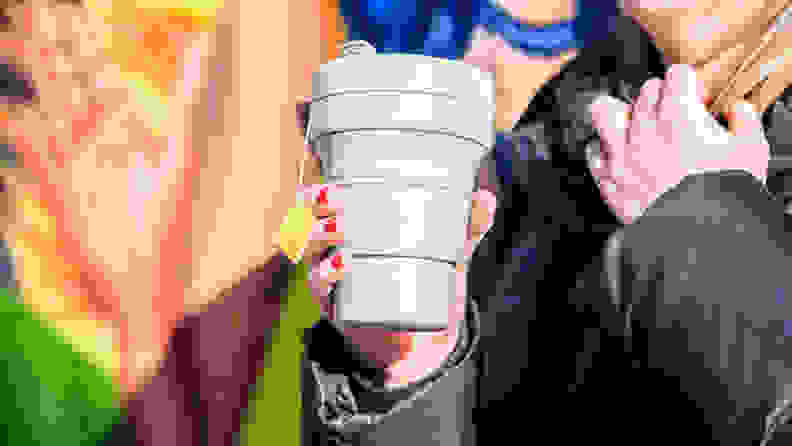 A photo of a woman holding the Stojo Cup.