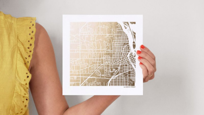 A woman holding a custom gold map