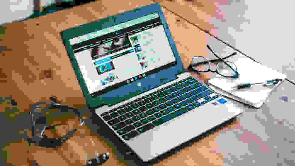 HP Chromebook sitting on a table next to glasses, a notebook, and some wires