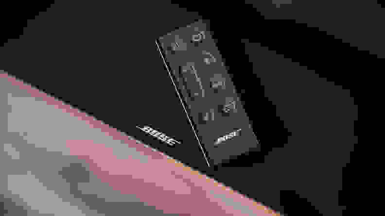 The Bose TV Speaker remote resting on top of the all-black soundbar, the white Bose logo peaking out beneath the slim rectangular remote with bubbled buttons on top.