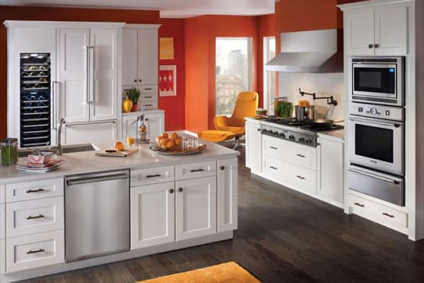 Striking contemporary orange kitchen with orange accents, outfitted with a Thermador 24-inch Sapphire series dishwasher, 48-inch rangetop, and 30-inch combination wall oven.