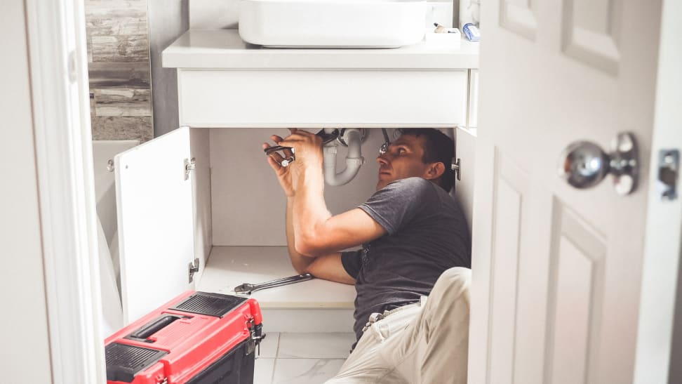 Person under sink fixing leak.