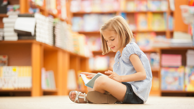 Girl reading book in library.