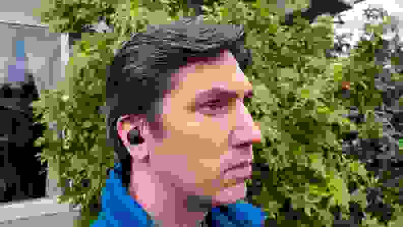 The black and rounded Sony WF-C500 earbud sits in the ear of a man with brown and silver hair, wearing a blue puffy vest in front of a bush.