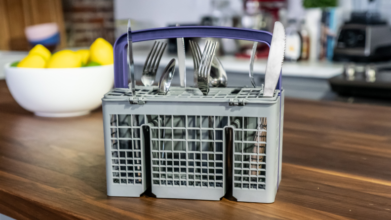 A dishwasher's cutlery basket sits on a counter in front of a bowl of lemons