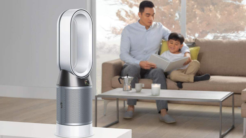 A parent and child sit in a living room with an air purifier.