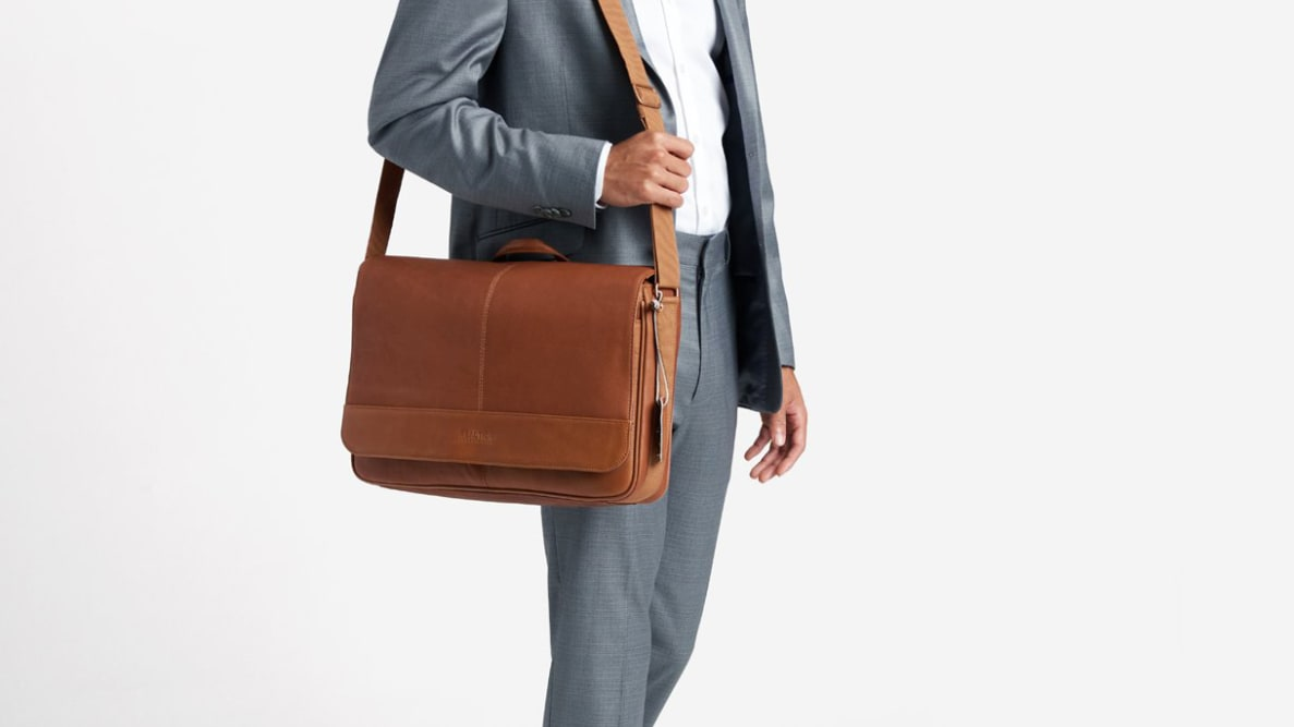 A person in a suit carrying a leather messenger bag.