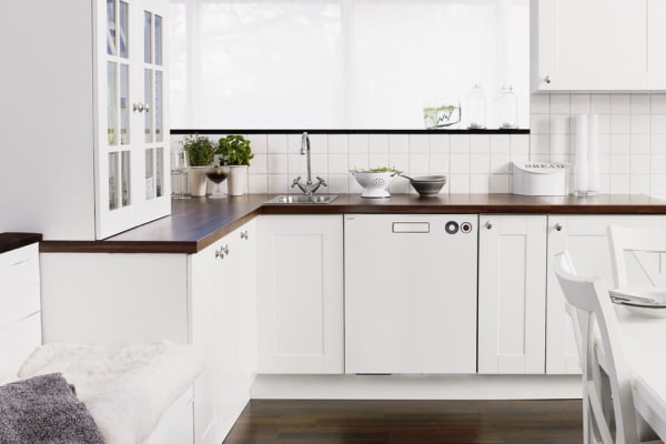 An Asko D5424WH dishwasher matched to the surrounding cabinetry of a traditional kitchen layout.