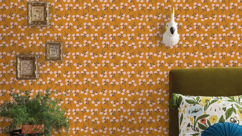 An orange wallpaper with lollipop style florals. Three small picture frames hang on the wall on the left side of the photo. On the right a parrot bust hangs on the wall over a bed.
