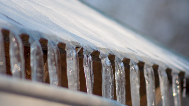 An ice dam is a thick layer of ice that forms on your roof, usually along the edge or in valleys, when melting water isn't able to drain away and refreezes.