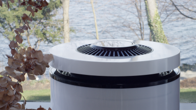 CleanAirZone bio-based air purifier in front of an outdoor landscape of trees and water