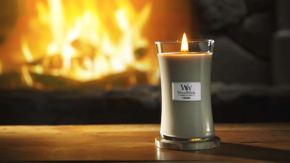 A lit WoodWick candle sits on a table in front of a fireplace.