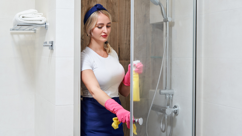 Woman wearing pink leather gloves to glass shower door.