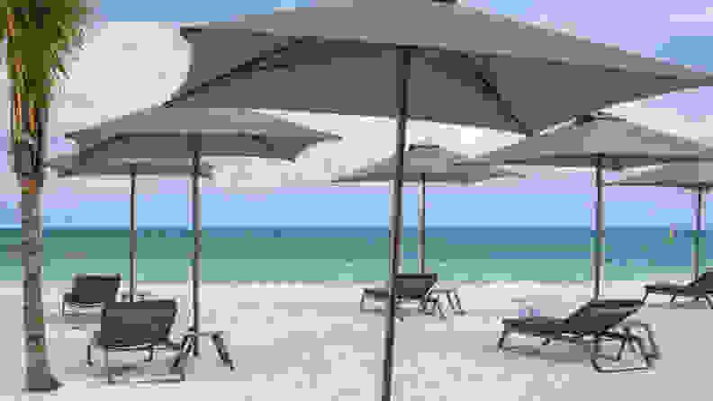 A photograph of a beach in Mexico with four beach umbrellas open
