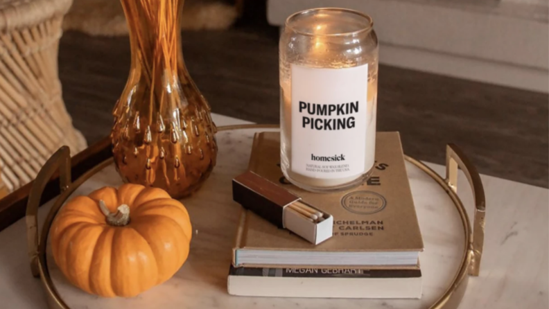 A pumpkin candle sitting on two books next to matches, a vase, and a mini pumpkin on a marble tray.