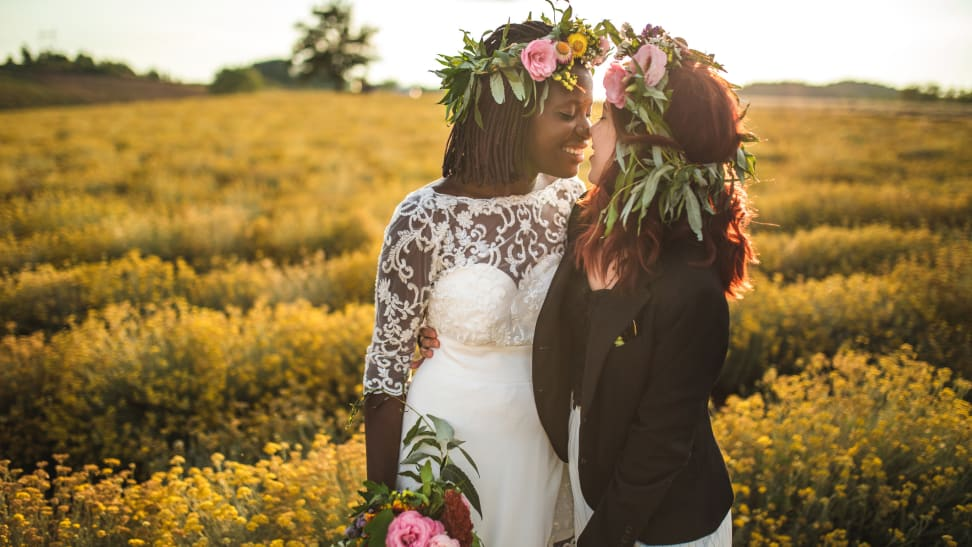 A Black human in a wedding dress and white human in a suit celebrate their wedding day, leaning in for a kiss.