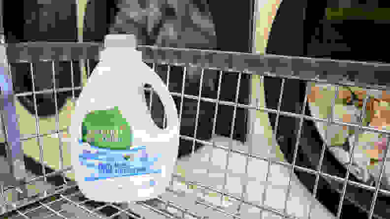 A bottle of Seventh Generation laundry detergent sitting in a laundry trolley in front of a row of washing machines.