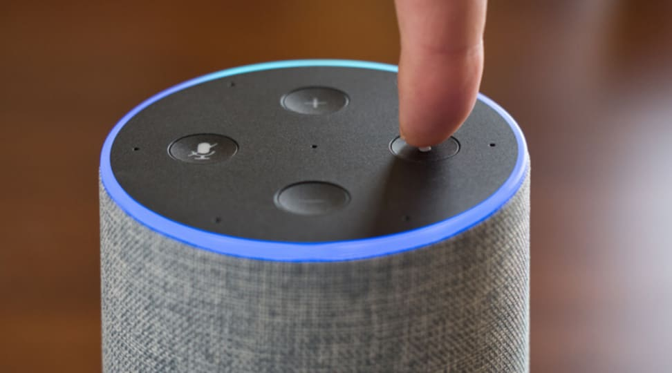 A finger presses buttons on an Amazon Echo smart speaker