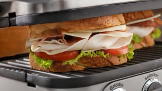 A sandwich  being cooked on an indoor grill.