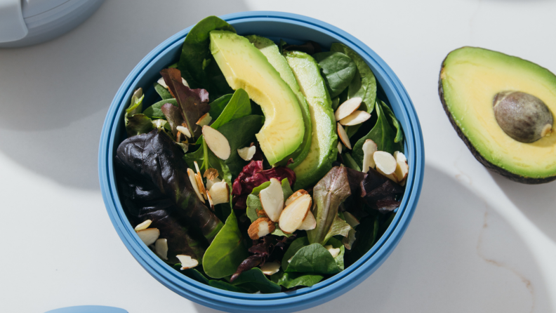 In the center of the image, there's a Stojo bowl filled with salad with sliced avocado and almonds on top. A half avocado is next to it.