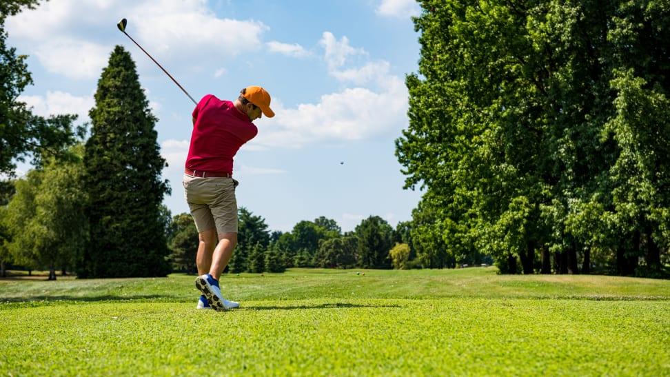 A golfer teeing off.