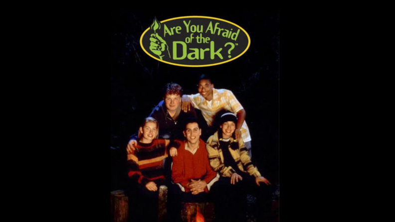 An image of the title card for Are You Afraid of the Dark? featuring teens around a campfire.