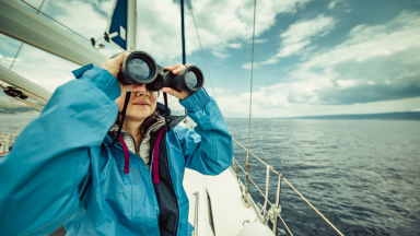 Girl on a boat using binoculars.