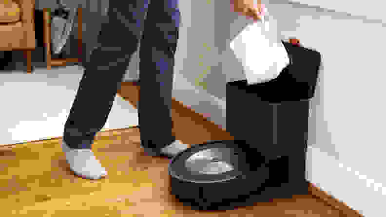 A self-sealing bag being removed from the iRobot Roomba J7+ charging base.