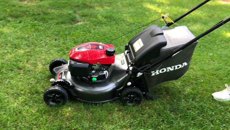 A Honda HRN216VKA lawn mower is pushed across a green lawn.