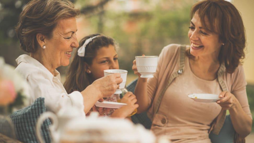 A grandmother, granddaughter, and mother sip tea in a garden.