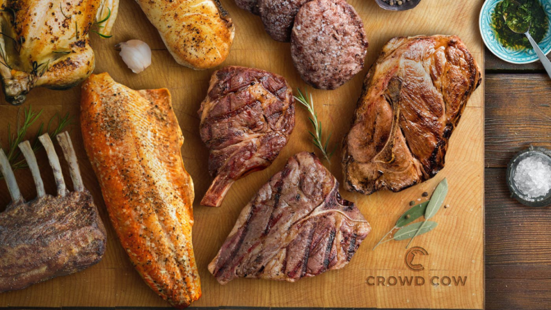 Various meat cuts spread out on a wooden cutting board.
